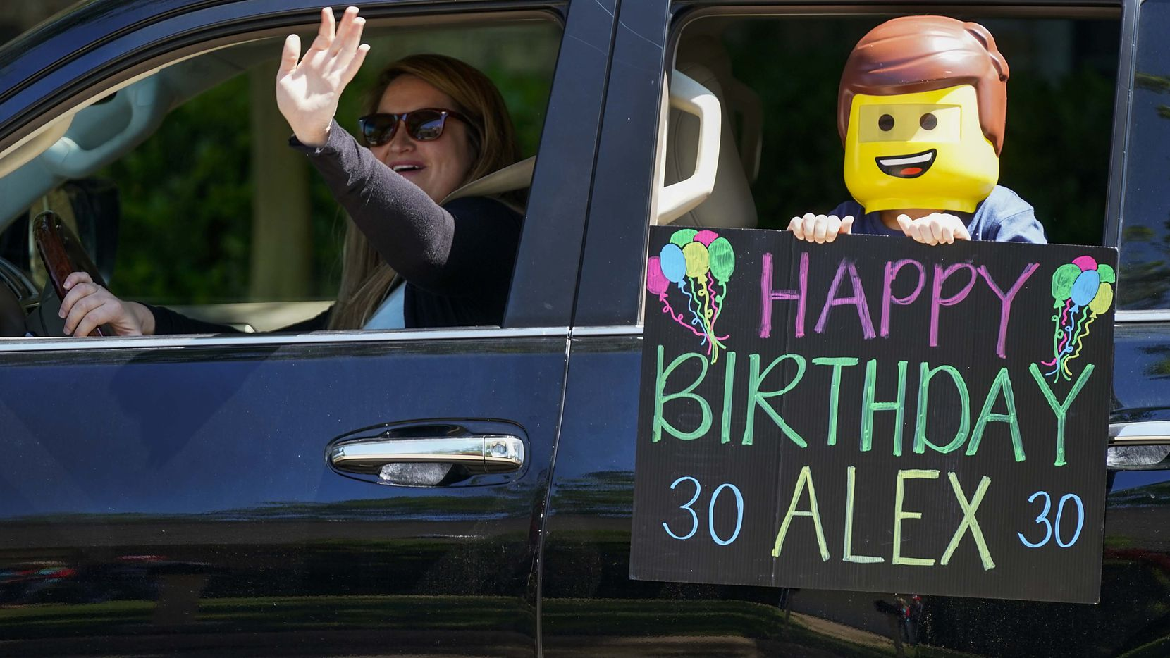 People waved and held signs while driving in a surprise parade of autos passing in front of the home of Alex Patterson to wish him a happy birthday on April 13 in Plano.