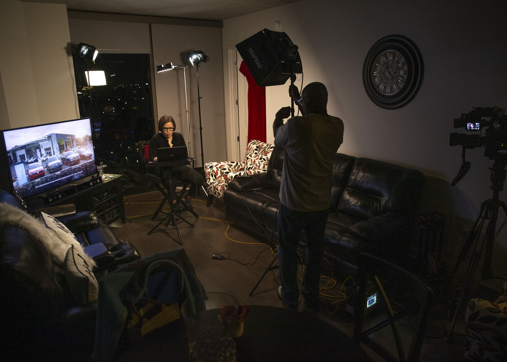 KXAS-TV (NBC5) morning anchor Laura Harris (left) prepares to broadcast live from her apartment home as photojournalist Dennis Holmes adjusts the set-upÕs lighting in Dallas on Friday, March 27, 2020. In light of CDC recommendations to practice social distancing, TV news broadcasts have incorporated segments of anchors working from home in order to set a good example for the community. (Lynda M. Gonzalez/The Dallas Morning News)