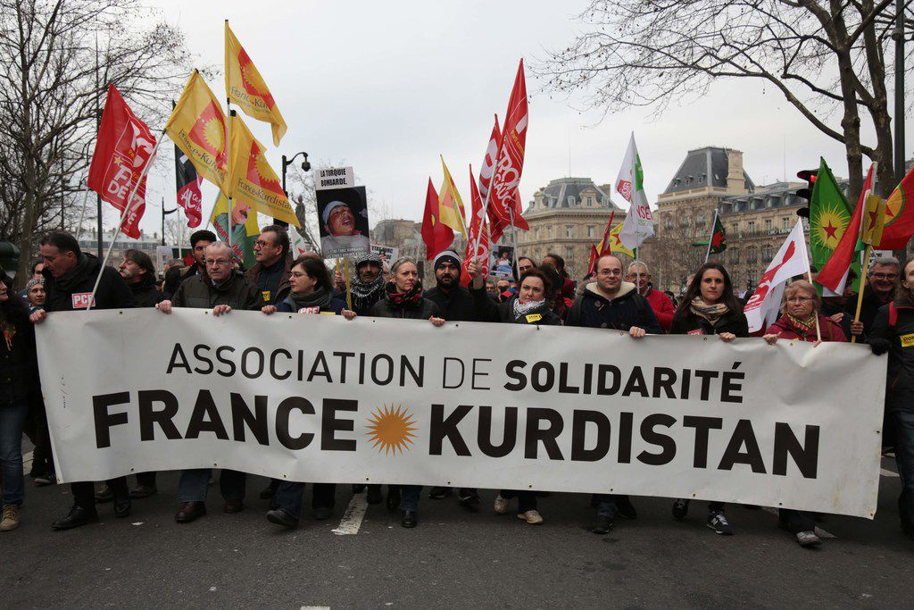 """People carry a banner during a demonstration against Turkey's military action in the Syrian town of Afrin, part of Operation Olive Branch, on Jan. 27, 2018 in Paris.  Turkey launched its military operation dubbed """"Olive Branch"""" against the Kurdish militia on Jan. 20, supporting Syrian rebels with ground troops, air strikes and artillery fire."""