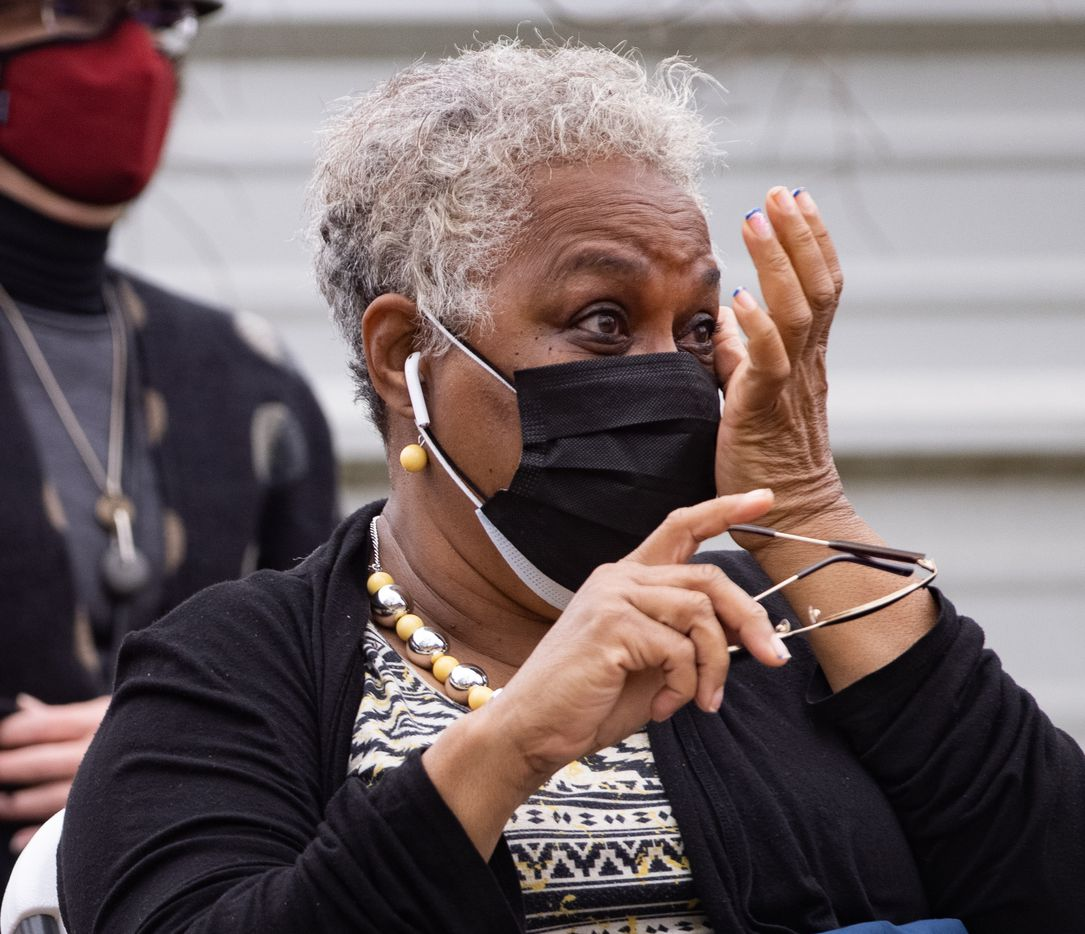 Marsha Jackson wipes her eyes while listening to opera singer Lawrence Brownlee perform outside of her home in Dallas on Friday, Feb. 26, 2021. Quincy Roberts, the contractor who moved Shingle Mountain, surprised Jackson with the concert. (Juan Figueroa/ The Dallas Morning News)