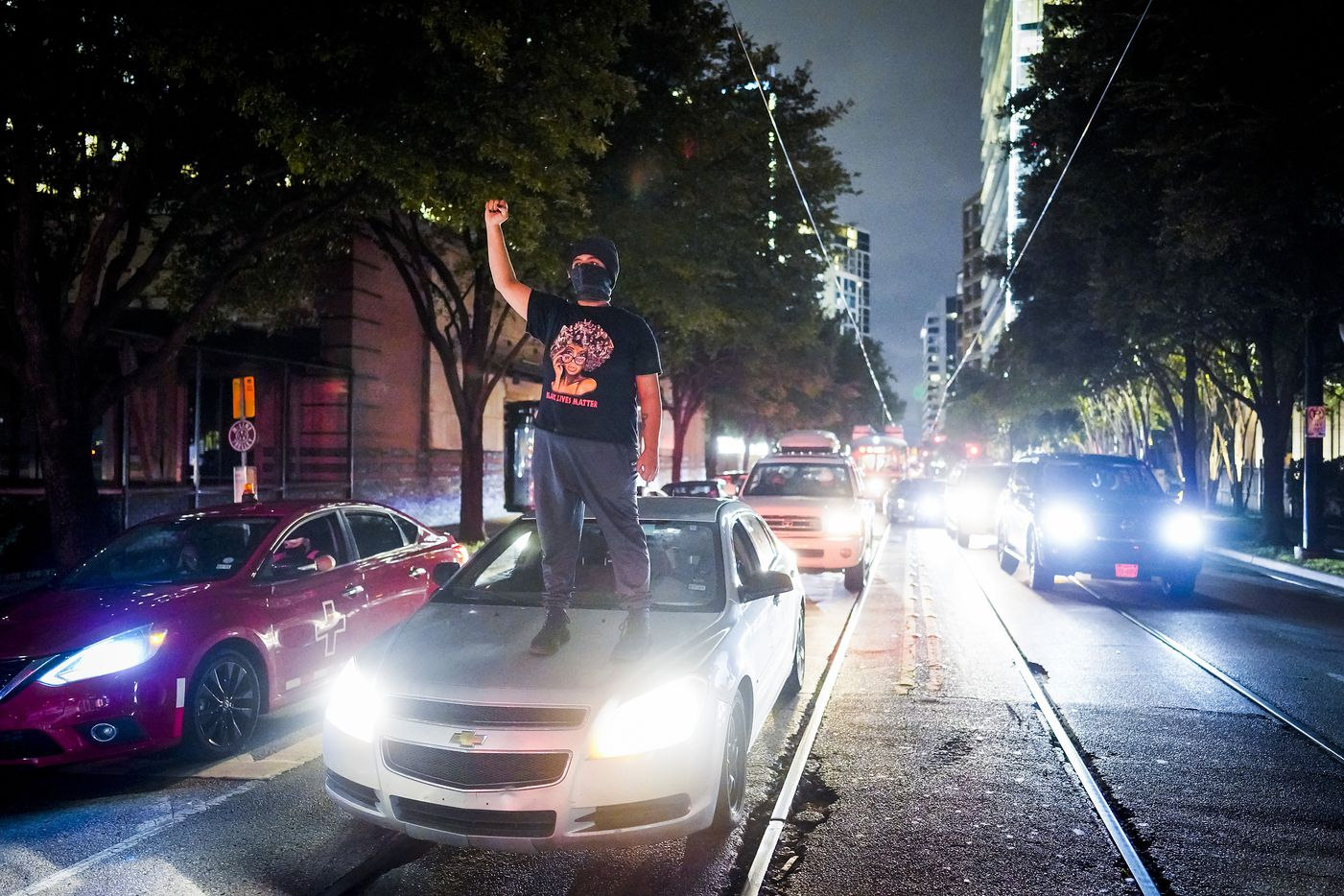 A demonstrator stands atop a car as protesters block the intersection of  McKinney at Pearl as they march through the Uptown after a Kentucky grand jury brought no charges against Louisville police for the killing of Breonna Taylor on Wednesday, Sept. 23, 2020.