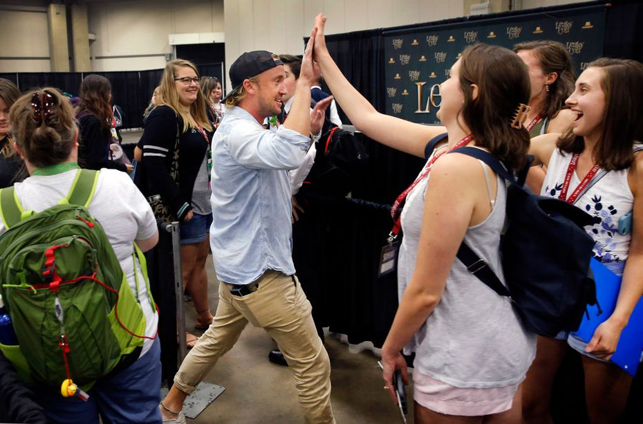 Draco Malfoy -- err, Harry Potter actor Tom Felton -- gives high-fives to fans before signing autographs during LeakyCon, a Harry Potter convention in Dallas.
