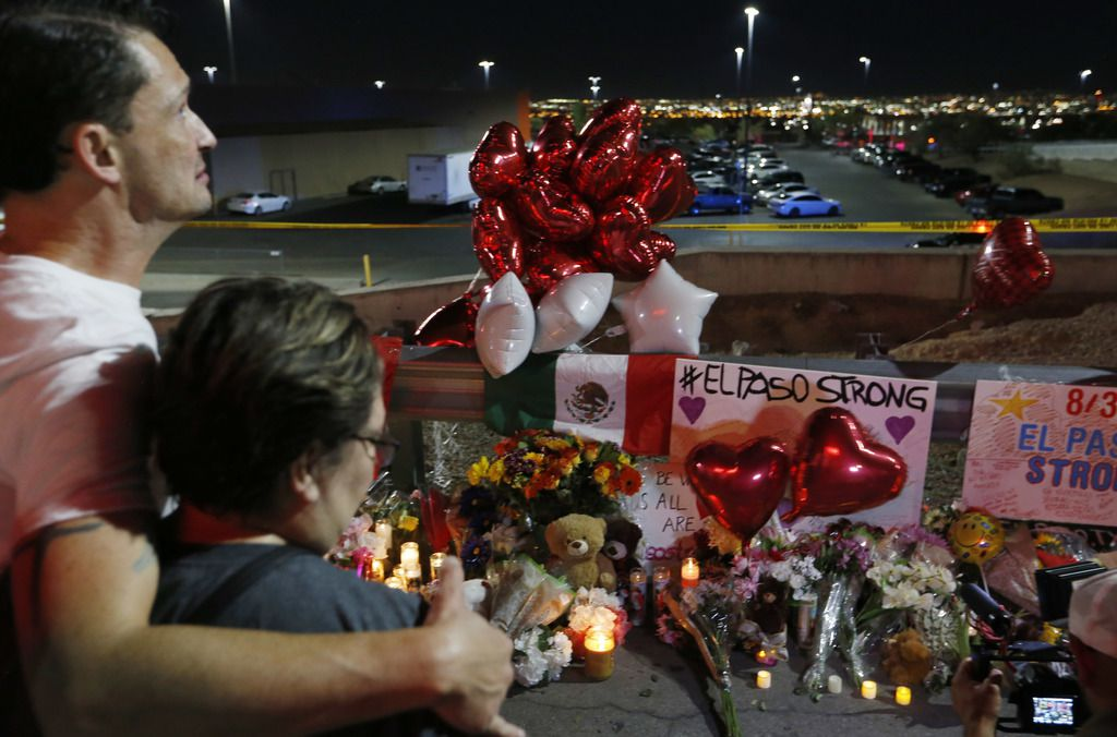People gather at the site of a makeshift memorial for victims of the mass shooting at the shopping complex near the Walmart in El Paso on August 5, 2019, two days after a shooting there left 22 people dead. (Vernon Bryant/The Dallas Morning News)