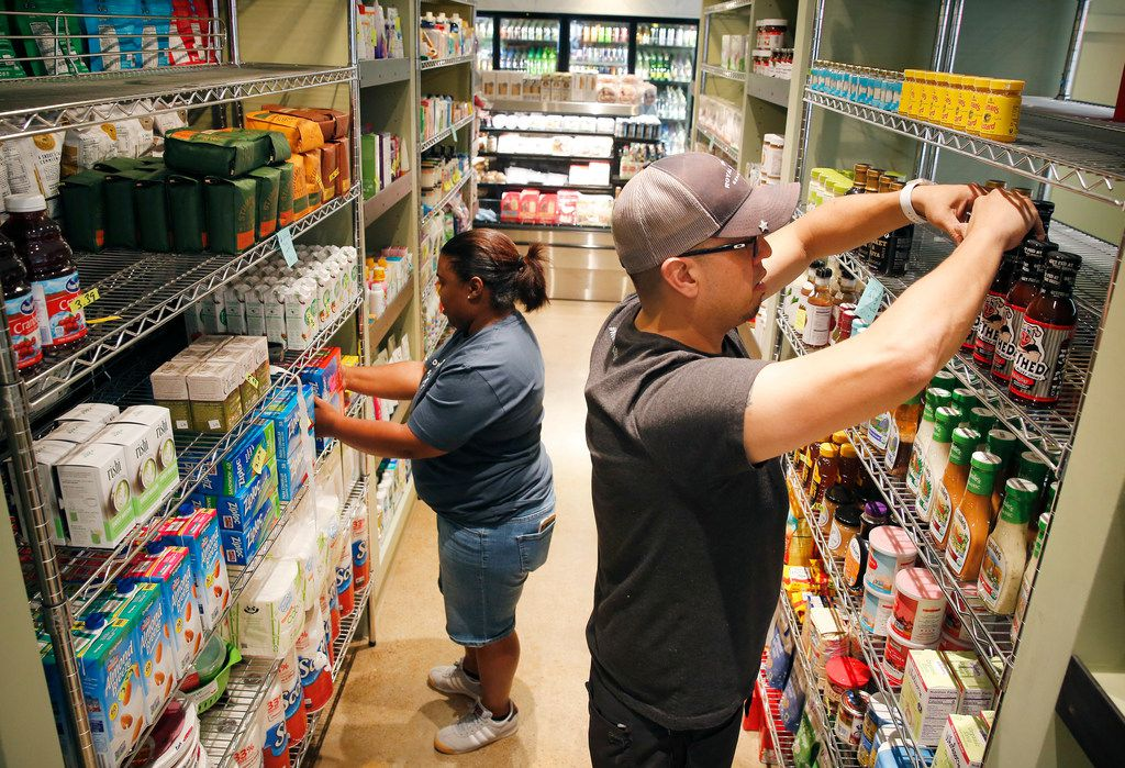 General manager Nathan Hartkopf  (right) and cashier Ozzie Massey stock shelves at the soon-to-open Royal Blue Grocery at Main and Ervay streets in downtown Dallas, Friday, July 27, 2018. (Tom Fox/The Dallas Morning News)