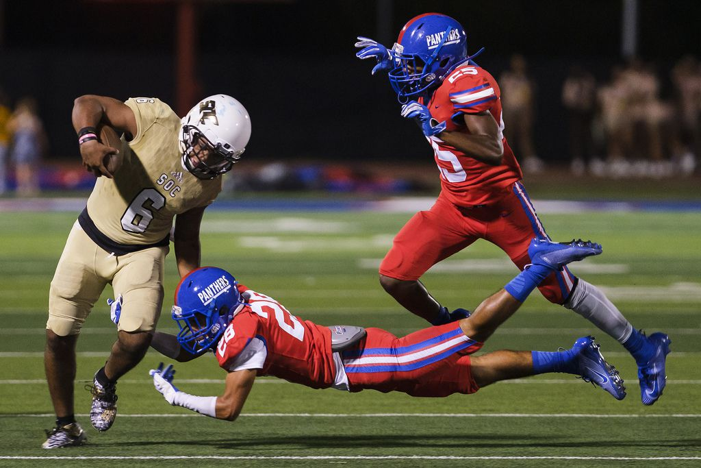 South Oak Cliff quarterback Rodney Hudson (6) is brought down by Duncanville defensive backs Awtavius Griffin (28) and Thailan Scott (25) during first half of a high school football game on Friday, Sept. 6, 2019, in Duncanville. (Smiley N. Pool/The Dallas Morning News)