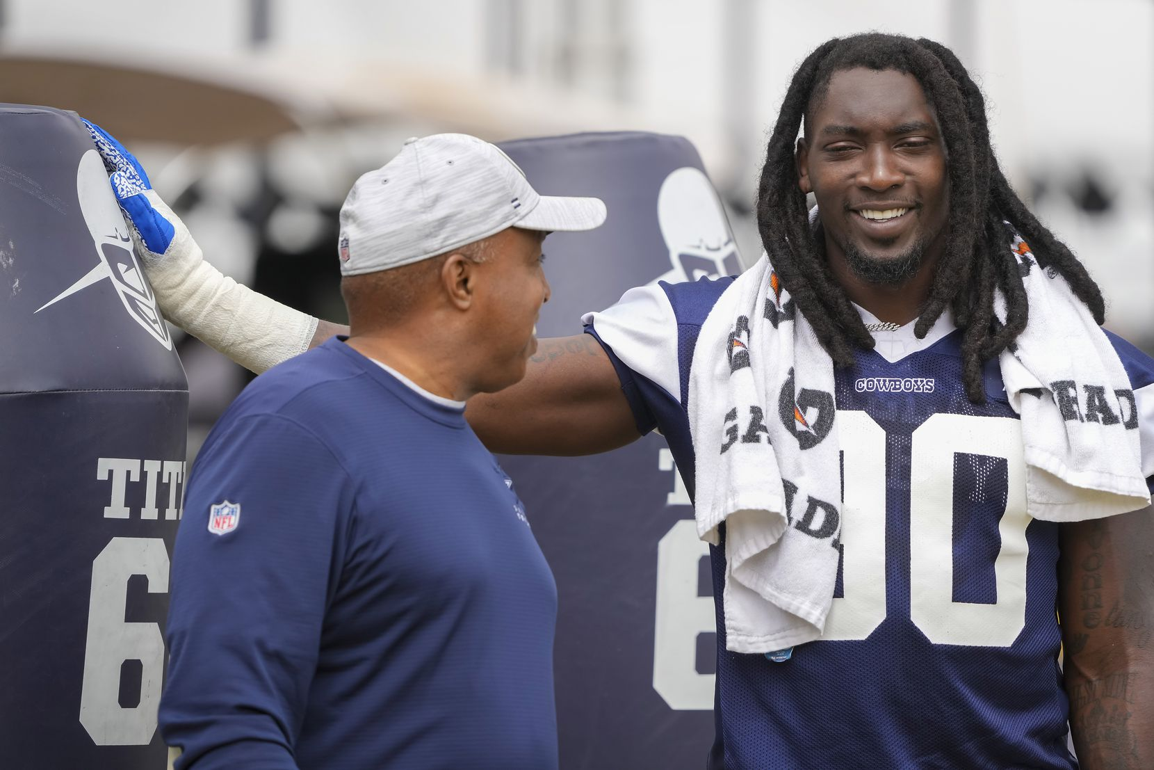 Dallas Cowboys defensive end DeMarcus Lawrence (90) laughs with sr. defensive assistantGeorge Edwards during a practice at training camp on Saturday, July 31, 2021, in Oxnard, Calif.