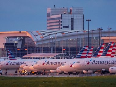 American Airlines aircraft sit parked on the ramp at DFW International Airport on Tuesday, April 14, 2020. About 25 planes are parked on a ramp to the south of Terminal D.