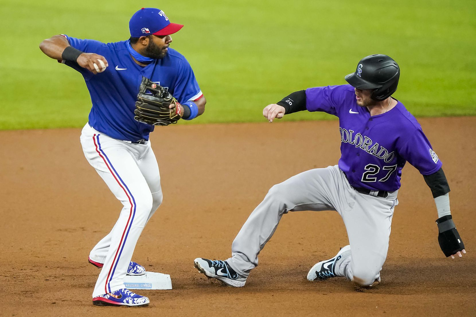 Colorado Rockies shortstop Trevor Story is out as second base as Texas Rangers shortstop Elvis Andrus turns a double play during the first inning of an exhibition game at Globe Life Field on Wednesday, July 22, 2020.