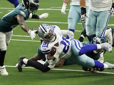 Dallas Cowboys running back Ezekiel Elliott (21) is brought down by the Philadelphia Eagles defense during the first quarter of an NFL football game at AT&T Stadium on Sunday, Dec. 27, 2020, in Arlington.
