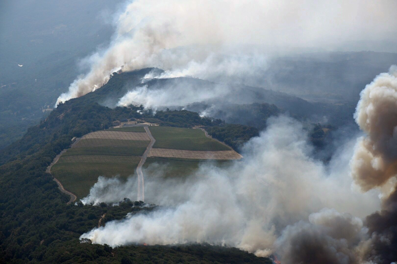 Smoke rises as a wildfire burns in the hills north east of Napa, Calif., Monday, Oct. 9, 2017. Wildfires whipped by powerful winds swept through Northern California sending residents on a headlong flight to safety through smoke and flames as homes burned.