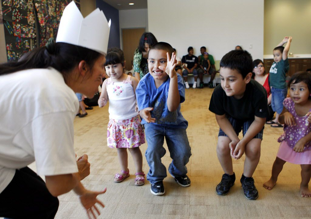 """Interactive reading activities is one of the key areas of training that mothers have participated in during the Hispanic Families Network training. Above, children at the Pleasant Grove Library act out a scene from """"Where the Wild Things Are."""" (DMN Photo)"""