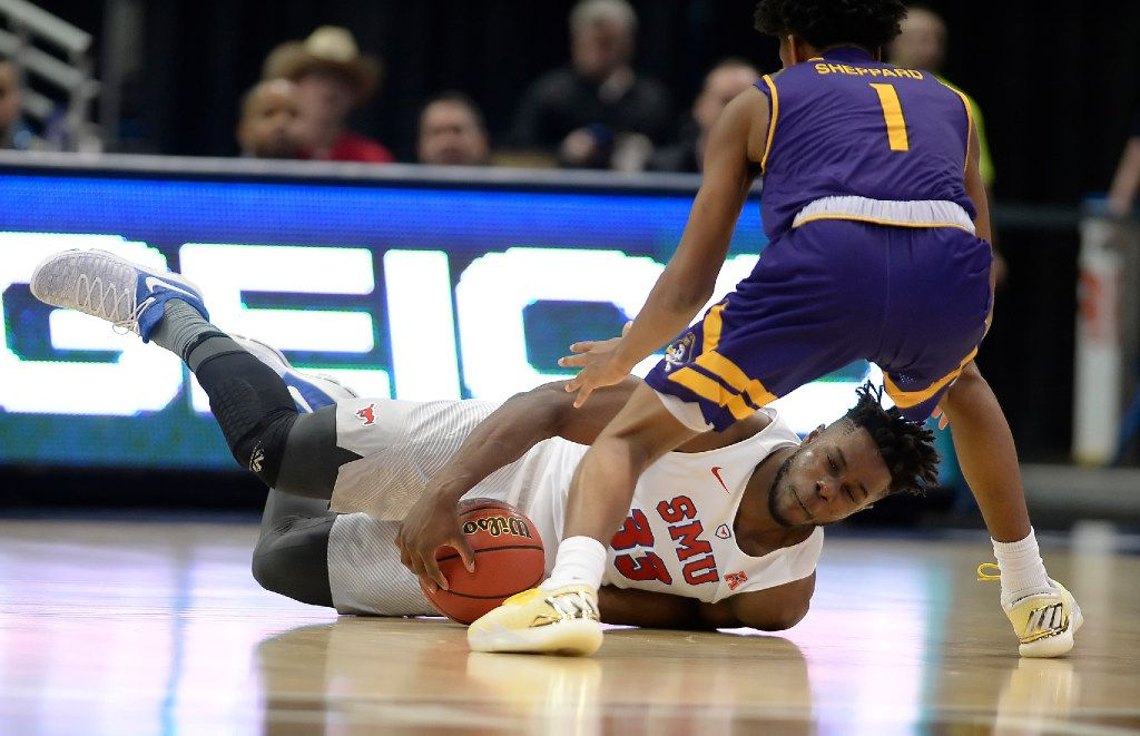 SMU's Semi Ojeleye dives for a loose ball as East Carolina's Jeremy Sheppard, left, defends, during the first half of an NCAA college basketball game in the American Athletic Conference tournament quarterfinals, Friday, March 10, 2017, in Hartford, Conn. (AP Photo/Jessica Hill)