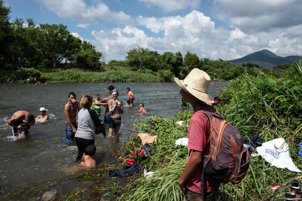"""Honduran migrants taking part in a caravan heading to the US, wash clothes and bathe in a river in Pijijiapan, Chiapas state, Mexico, on October 25, 2018. - The Pentagon is expected to deploy about 800 troops to the US-Mexico border, two US officials told AFP on Thursday, after President Donald Trump said the military would be used there to tackle a """"national emergency."""" (Photo by Guillermo Arias / AFP)GUILLERMO ARIAS/AFP/Getty Images"""