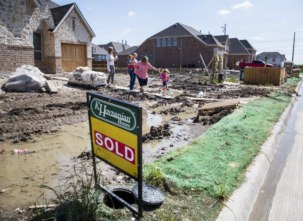 Sales Consultant Amy Woy, left, of K Hovnanian Homes follows home buyer Emily Barker of Plano, her daughters Nora Barker, 2, and Bryn Barker, 4, and Jill Renfro (second from right) out of a new home on Wednesday, May 20, 2015 at the Diamond Point Estates neighborhood in Frisco, Texas. (Ashley Landis/The Dallas Morning News)