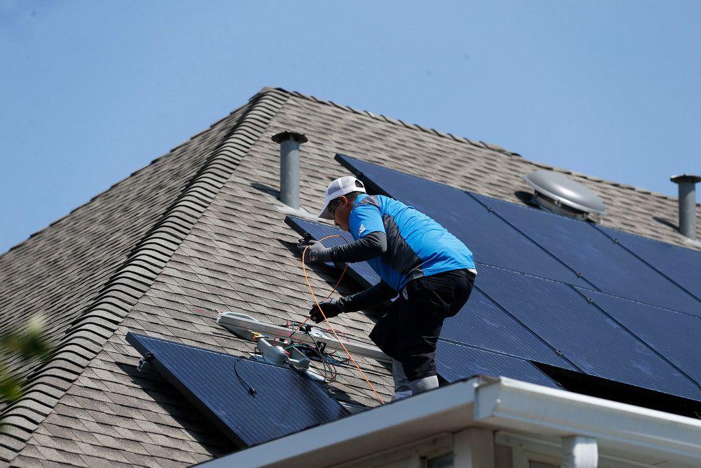 Roland Montoya, lead solar installer with Kosmos Solar, installs solar panels on a home in Arlington, Texas on Wednesday, Sept. 20, 2017. (Rose Baca/The Dallas Morning News)