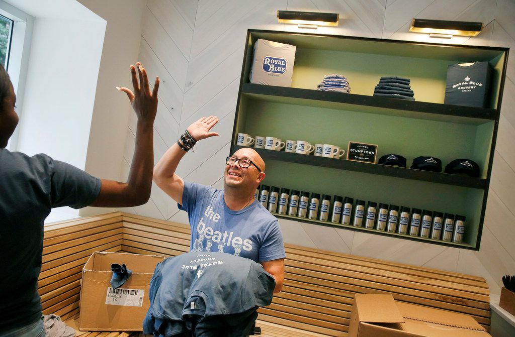 Cashier Francisco Dominguez (right) receives a high five from co-worker Aniza Haynie after arranging t-shirts on a shelf at the soon-to-be-open Royal Blue Grocery at Main and Ervay streets in downtown Dallas, Friday, July 27, 2018. (Tom Fox/The Dallas Morning News)