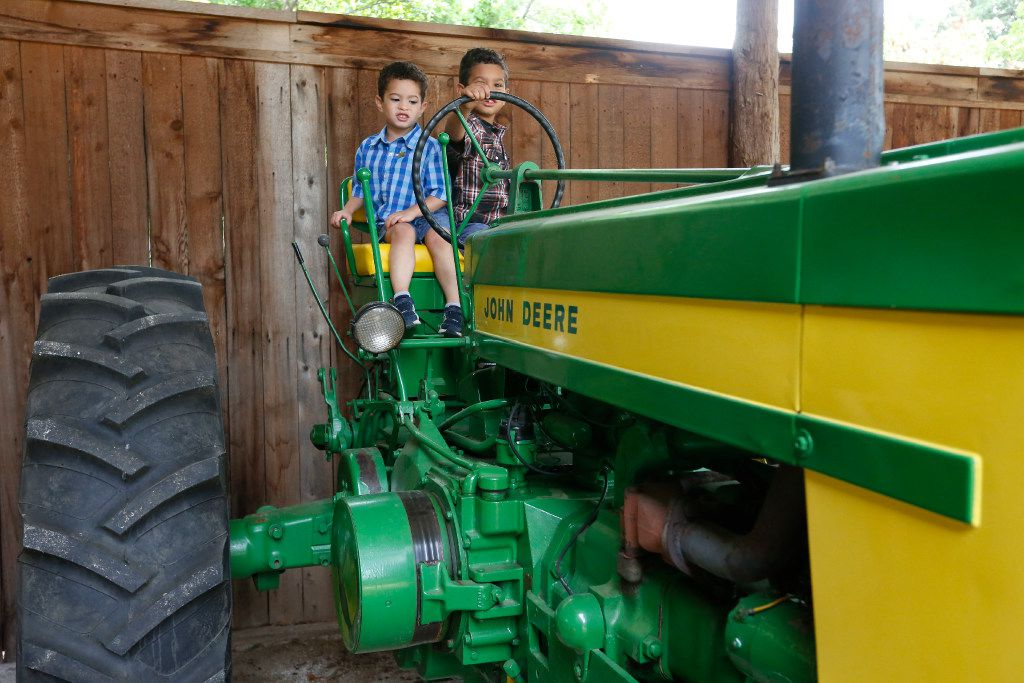 Sebastian Derry, 3, and his brother, Philip Derry, 5, of Keller, play on one of the tractors at Nash Farm in Grapevine.