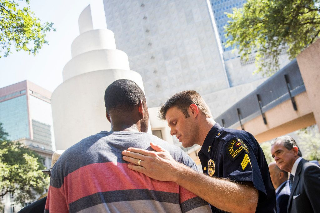 Dallas police Sgt. Dan Mosher hugs Odell Edwards, the father of Jordan Edwards, a 15-year-old who was killed by a Balch Springs police officer in April, during a day of remembrance for last year's police ambush organized by Faith Forward Dallas at Thanks-Giving Square on Friday, July 7, 2017, in Dallas.