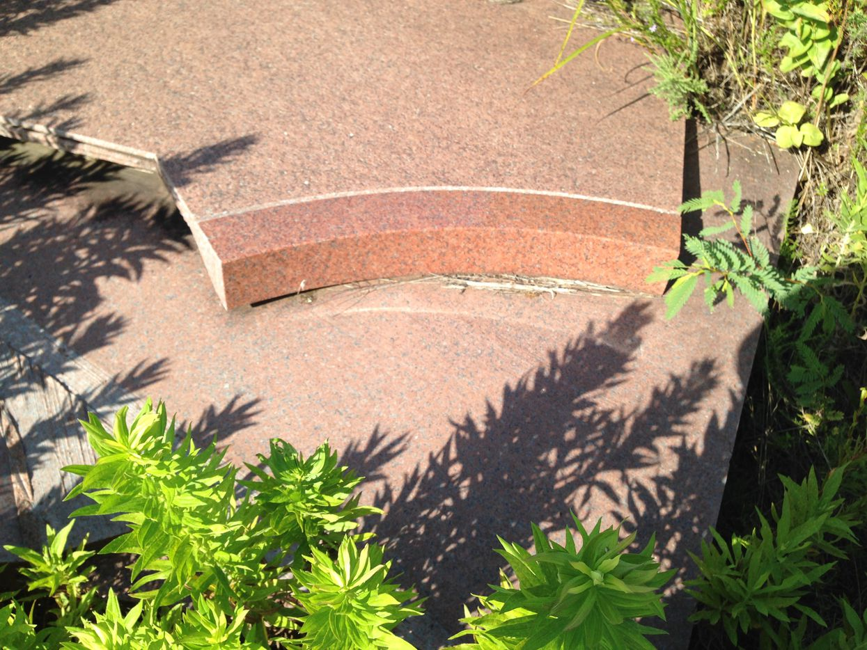 Cut and polished stone that was to surround a window on the second Cityplace tower is home to weeds and grasshoppers.