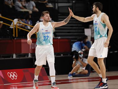 Slovenia's Luka Doncic (77) and Mike Tobey (10) celebrate after a made basket against Japan in a basketball game during the second half of play at the postponed 2020 Tokyo Olympics at Saitama Super Arena on Thursday, July 29, 2021, in Saitama, Japan. Slovenia defeated Japan 116-81. (Vernon Bryant/The Dallas Morning News)