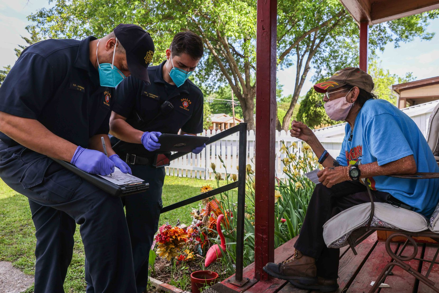 Dallas Fire-Rescue medic Corey Nix and driver engineer Robert Kober fill out paperwork from Albert Garza after he received the first dose of the Moderna vaccine as a resident enrolled in the Visiting Nurse Association of Texas' Meals on Wheels program.