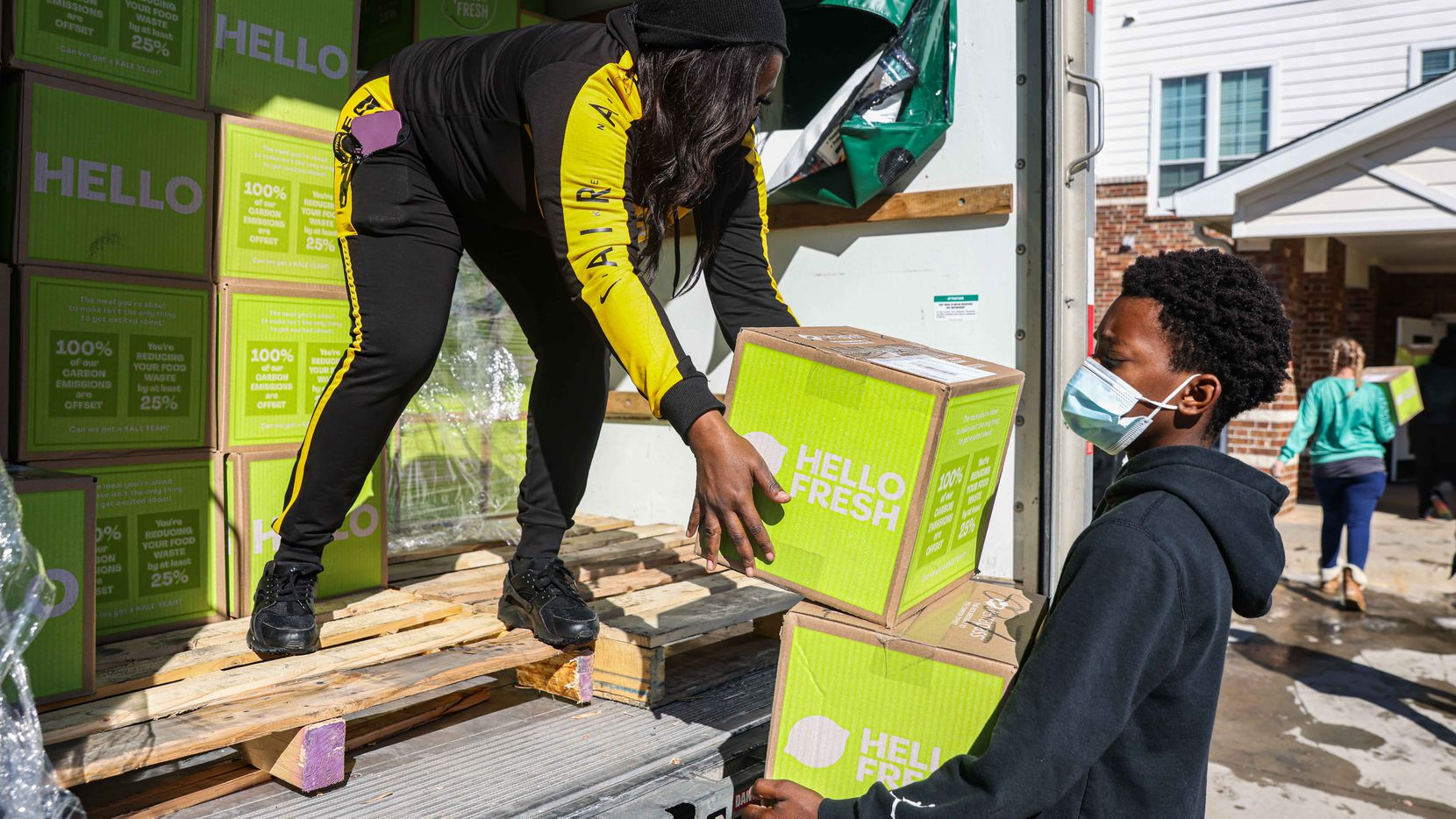 Local volunteer Sonya Tubbs with the help of Marcus Thomas, 13, bring boxes of food for the community of Lakewest Senior Housing at Westmoreland Heights in Dallas on Saturday, February 20, 2021. The community is still without water after snow storm Uri hit Dallas this week. (Lola Gomez/The Dallas Morning News)