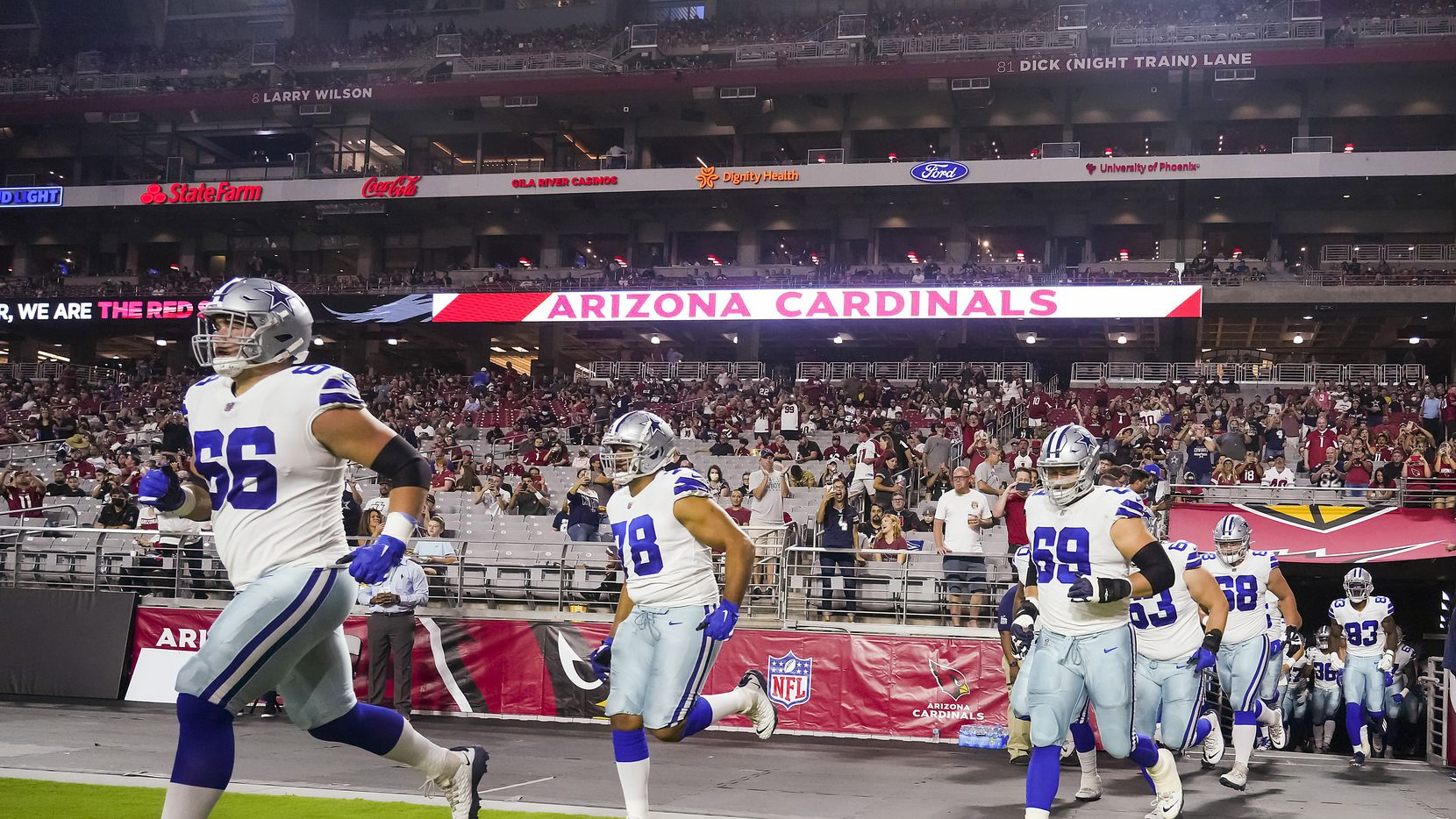 Dallas Cowboys guard Connor McGovern (66), tackle Terence Steele (78), Dallas Cowboys tackle Brandon Knight (69) lead teammates as they take the field before an NFL football game against the Arizona Cardinals at State Farm Stadium on Friday, Aug. 13, 2021, in Glendale, Ariz.