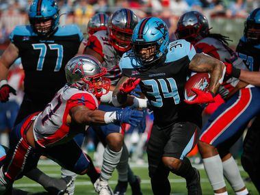 Dallas Renegades running back Cameron Artis-Payne (34) dodges the Houston Roughnecks defense during the first half on Sunday, March 1, 2020 at Globe Life Park in Arlington, Texas. The Renegades lost 20-27.