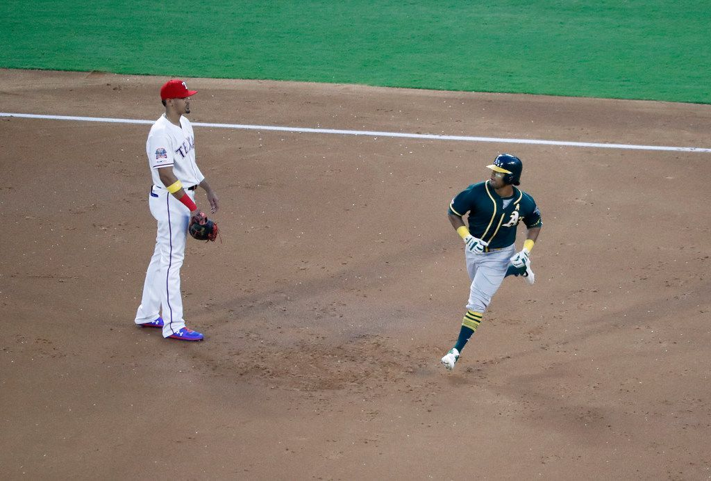 Texas Rangers' Ronald Guzman, left, looks on as Oakland Athletics' Khris Davis rounds the bases after hitting a solo home run in the second inning of a baseball game in Arlington, Texas, Friday, Sept. 13, 2019.