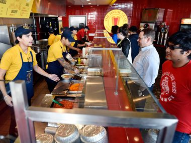 Food server Elijah Layton, left, takes an order from Amann Islam at the a The Halal Guys restaurant in this 2017 file photo. Ben Torres/Special Contributor