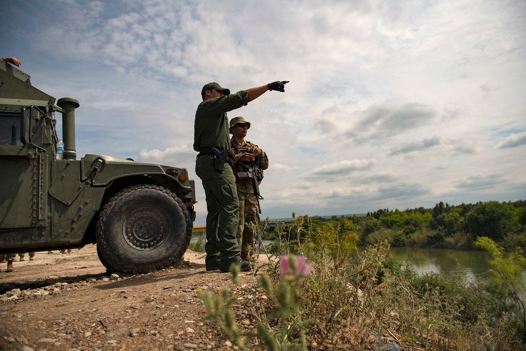 A Border Patrol officer talked with a member of the Texas National Guard along the Rio Grande in Starr County, Texas, April 10, 2018. As the National Guard begins a controversial mobilization on the southern border, soldiers are trying to fulfill two seemingly contradictory missions: standing out, and blending in. (Lynsey Addario/The New York Times)
