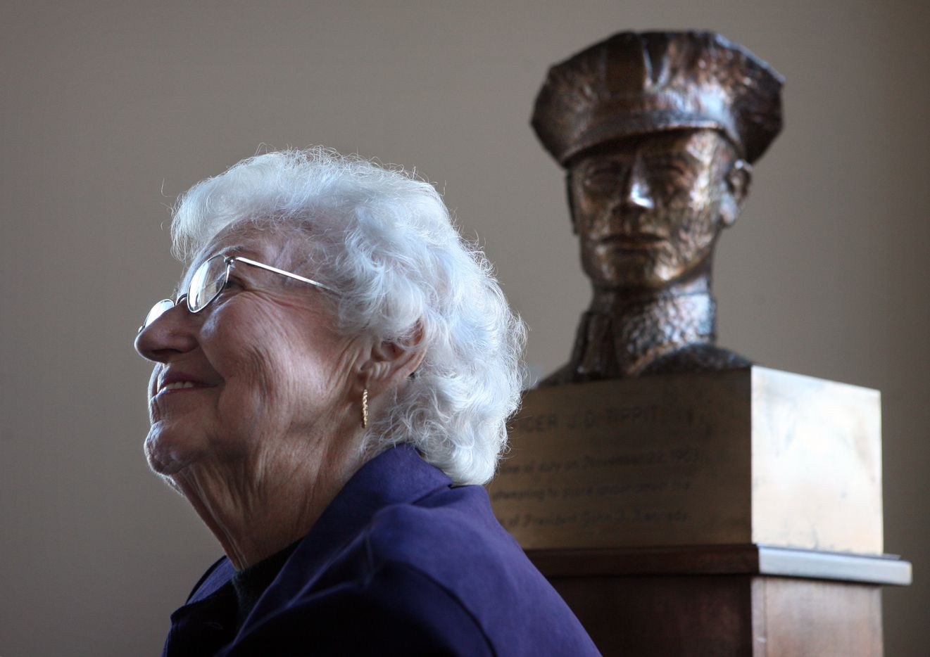 Marie Tippit near a bronze bust of husband J.D. Tippit at Dallas police headquarters in 2008.