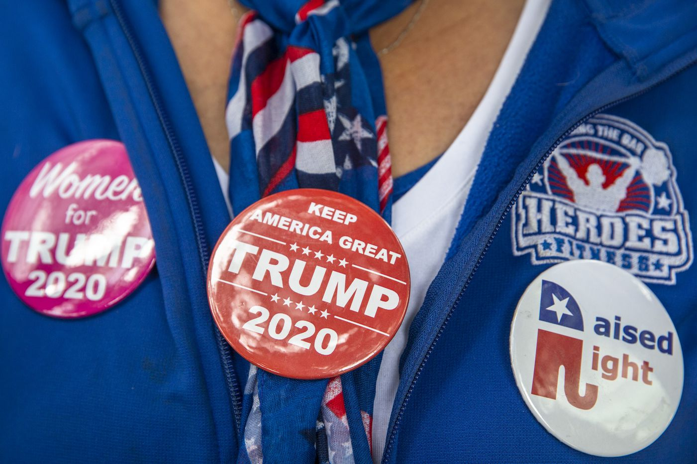 A supporter of President Donald Trump wears her new pins while camping out in line in front of the American Airlines Center in Dallas on Wednesday, Oct. 16, 2019. President Trump will host a rally at the center on Thursday evening.