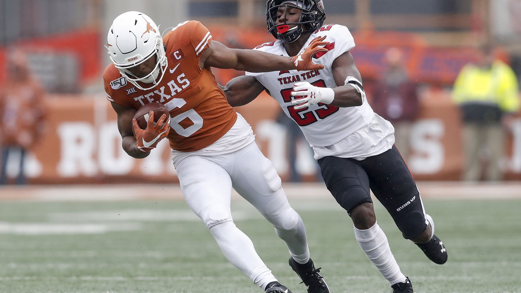 AUSTIN, TX - NOVEMBER 29:  Devin Duvernay #6 of the Texas Longhorns attempts to avoid a tackle by Damarcus Fields #23 of the Texas Tech Red Raiders in the second half at Darrell K Royal-Texas Memorial Stadium on November 29, 2019 in Austin, Texas.