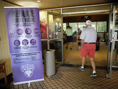 Golfers are reminded of ways to prevent coronavirus spread as they enter the pro shop at Grapevine Golf Course in Grapevine, Texas, Wednesday, May 27 2020.