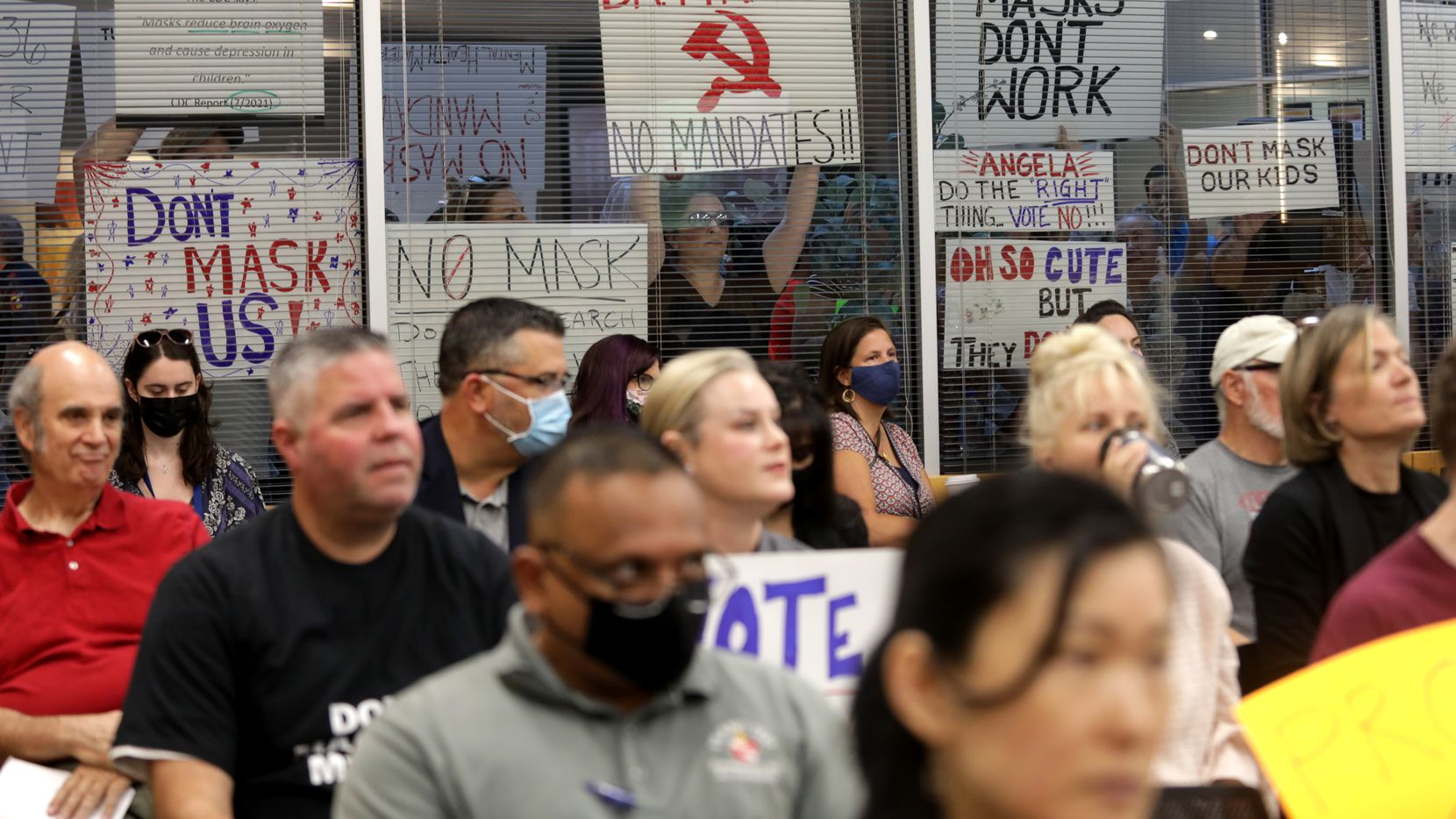 Community members on both sides of the masking debate gather during a Plano ISD emergency meeting regarding mask mandates at the Plano District Administration Building Board Room in Plano, TX, on Aug. 23, 2021.