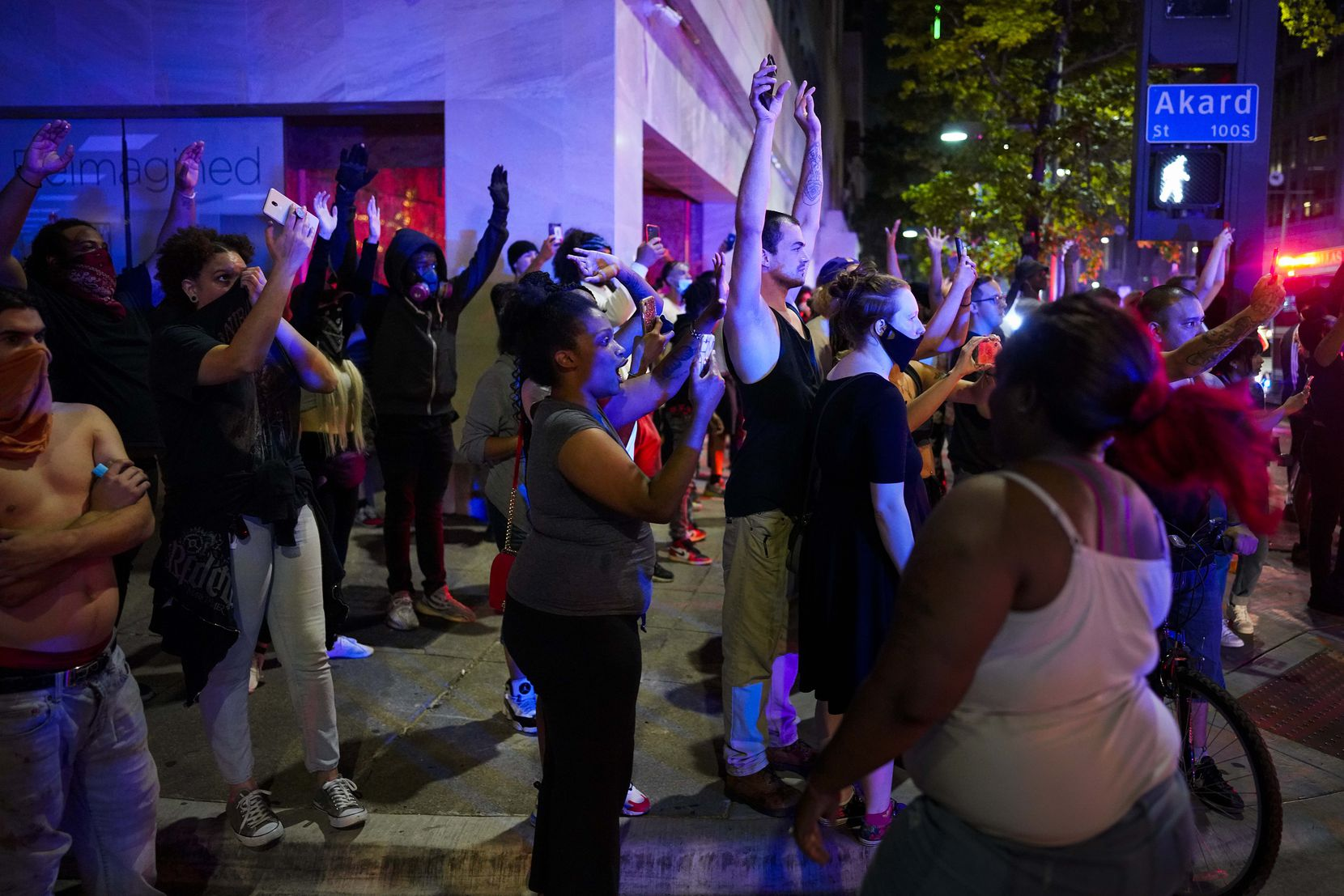 A group of people raise their hands at the corner of Akard and Main Streets downtown after being told to disperse, and immediately before teargas was deployed, by Dallas police following a protest against police brutality in the early morning hours of Saturday, May 30, 2020, in Dallas.