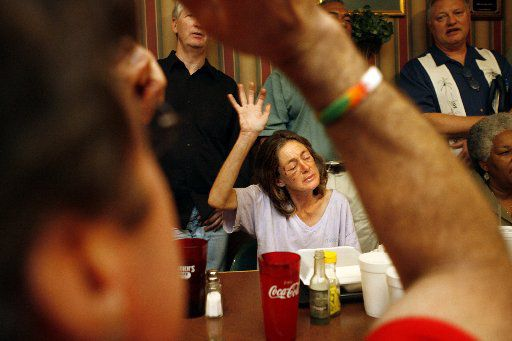 In this 2007 file photo, Sherry Mason, center, who's homeless, prays amidst businessmen, students and the occasional Dallas Cowboys football player during Holy Spirit Hospital bible fellowship on Tuesdays at Smokey John's in Dallas.