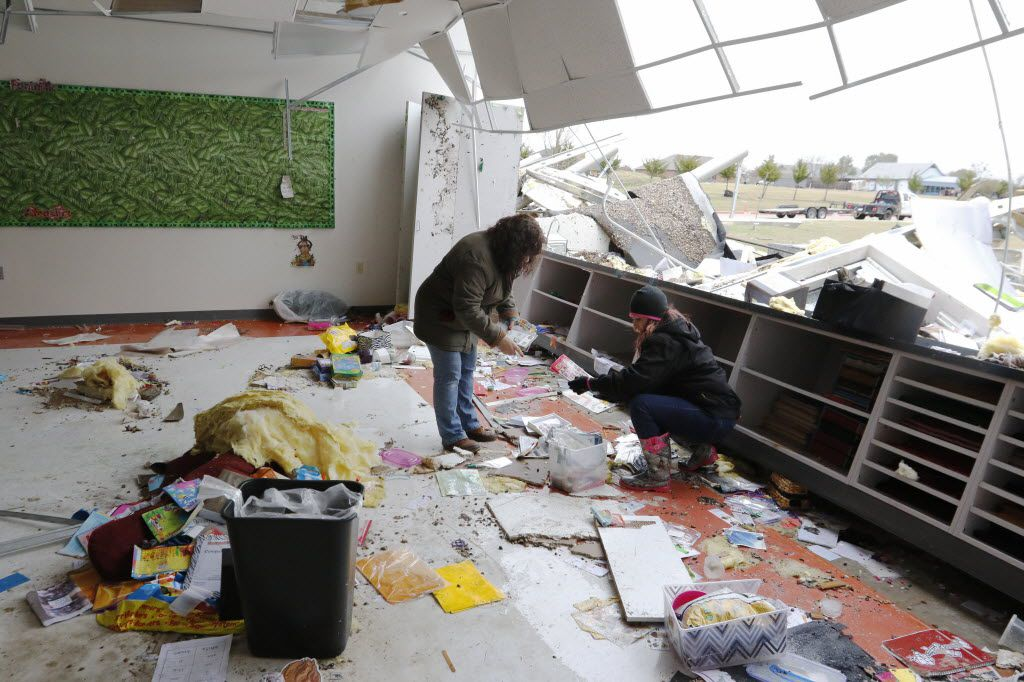 Viana Armstrong, left, and Christina Lediaev try to salvage school materials at the storm-damaged Donald T. Shields Elementary School in Glenn Heights on Dec.  28, 2015.  (David Woo/The Dallas Morning News)