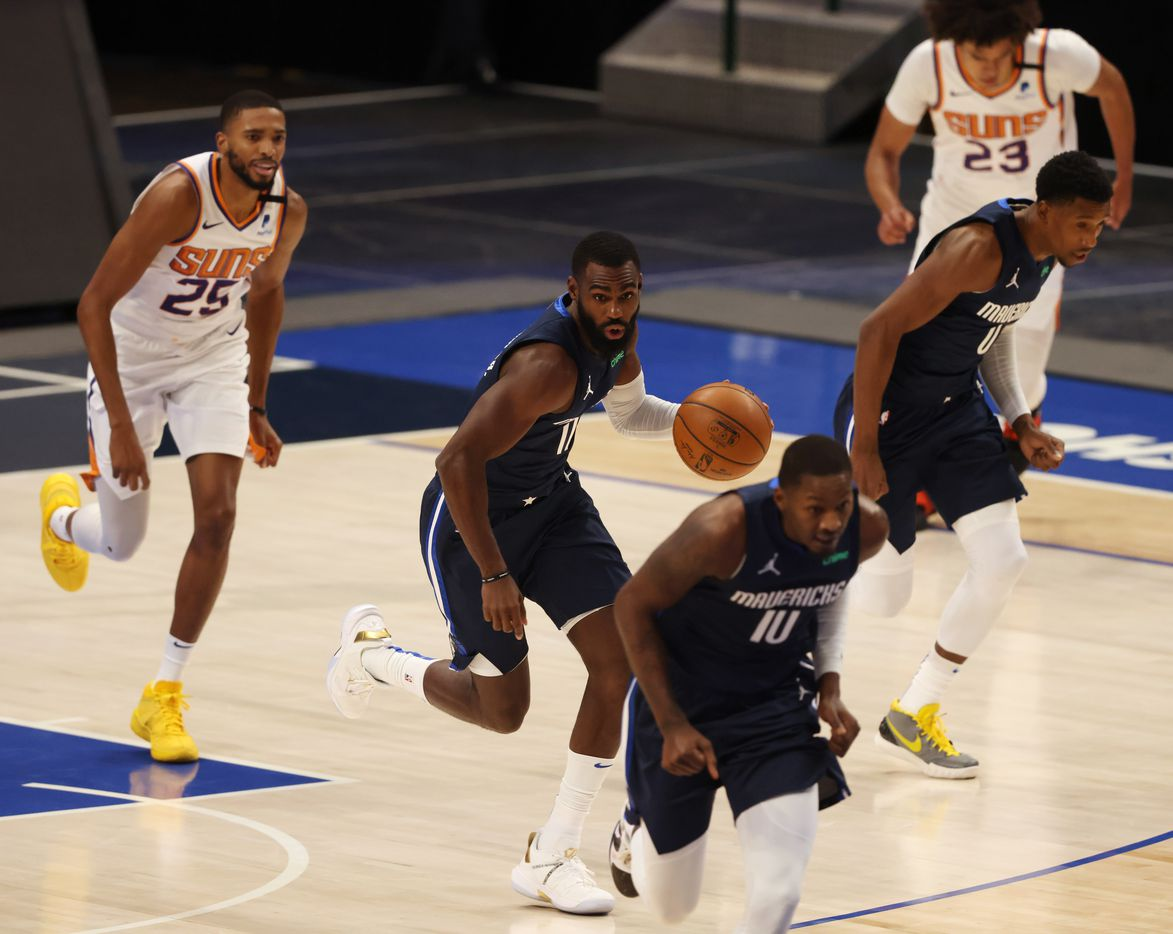 Dallas Mavericks forward Tim Hardaway Jr. (11) dribbles up the court as Phoenix Suns forward Mikal Bridges (25) follows during the first quarter of play at American Airlines Center on Monday, February 1, 2021in Dallas. (Vernon Bryant/The Dallas Morning News)