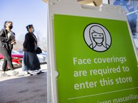 Shoppers pass by a face mask sign at the Ross in City Place in Dallas on Tuesday. Gov. Greg Abbott announced that all businesses can reopen at 100% capacity and also ended the mask mandate starting next Wednesday.