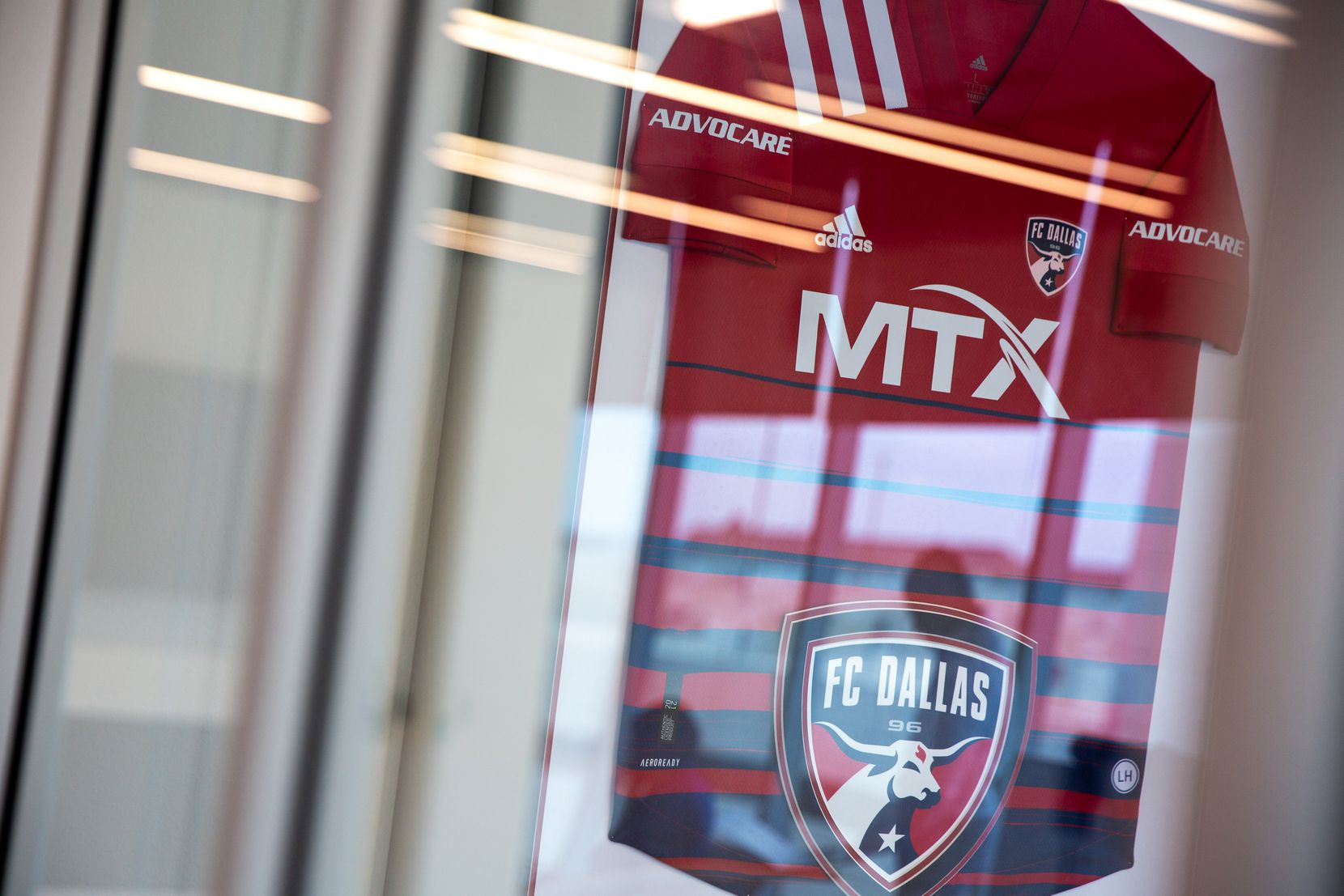 An FC Dallas jersey with the MTX name on it is framed in Nobel's Frisco office. MTX is a team sponsor.