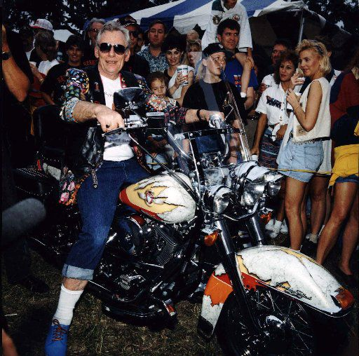 Straddling a Harley-Davidson motorcycle given him by his pilots, Southwest Airlines chairman Herb Kelleher prepares to sing 'Blue Suede Shoes' at a 1994 company chili cook-off in Dallas.