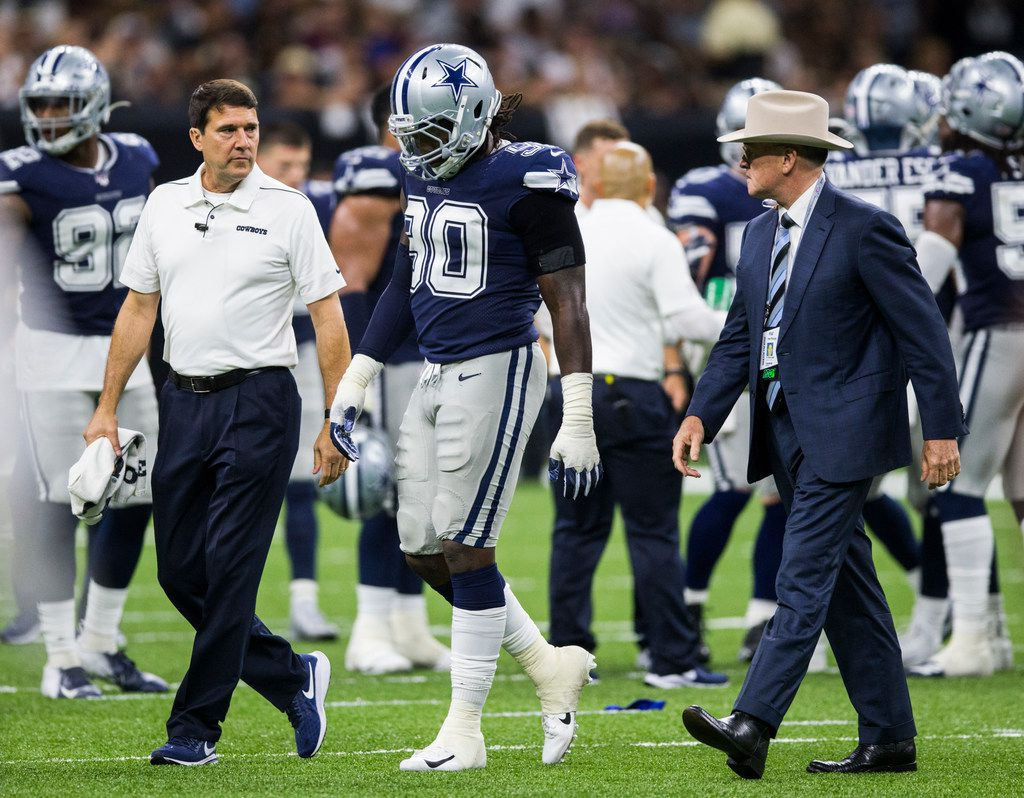 FILE - Dallas Cowboys defensive end Demarcus Lawrence (90) is escorted off the field after being checked out for injury during the fourth quarter of an NFL game between the Dallas Cowboys and the News Orleans Saints on Sunday, September 29, 2019 at Mercedes-Benz Superdome in New Orleans, Louisiana. (Ashley Landis/The Dallas Morning News)