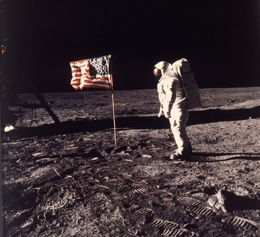 "In this July 20, 1969 file photo, astronaut Edwin E. ""Buzz"" Aldrin Jr. stands next to a U.S. flag planted on the moon during the Apollo 11 mission. Aldrin and Neil Armstrong were the first men to walk on the lunar surface. (Neil A. Armstrong/NASA via AP)"