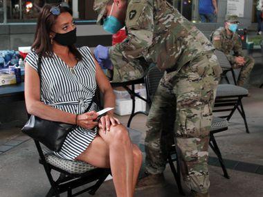 Xavian Flores, de la reserva del ejército vacuna a Ashley Shalz in Victory Plaza poco antes de un partido de los Mavs, como parte de una clínica móvil de vacunación. Este fin de semana habrá vacunaciones en Oak Cliff y Oak Lawn.
