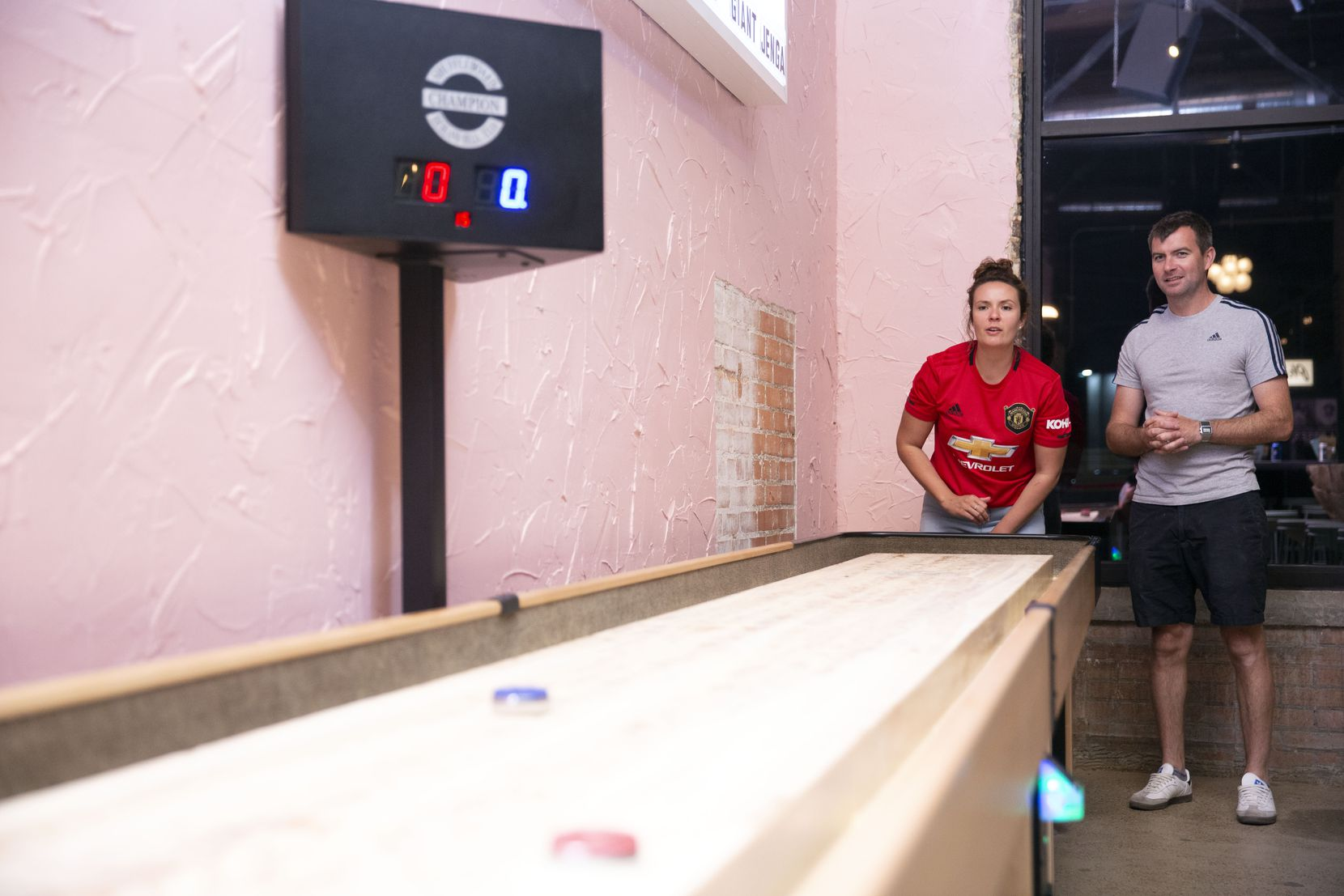 Pia Barnett, left, and Chris Hill, right, play shuffleboard at Punch Bowl Social. This photo was taken pre-pandemic, in 2019.