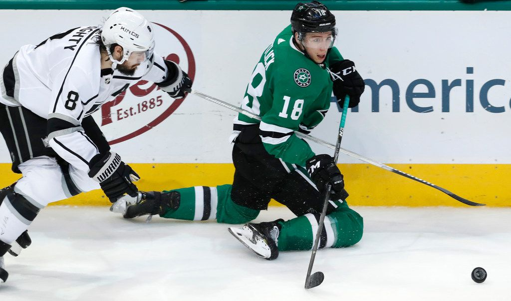 Dallas Stars center Tyler Pitlick (18) and Los Angeles Kings defenseman Drew Doughty (8) reach for the puck during the second period of an NHL hockey game in Dallas, Thursday, Jan. 17, 2019. (AP Photo/LM Otero)