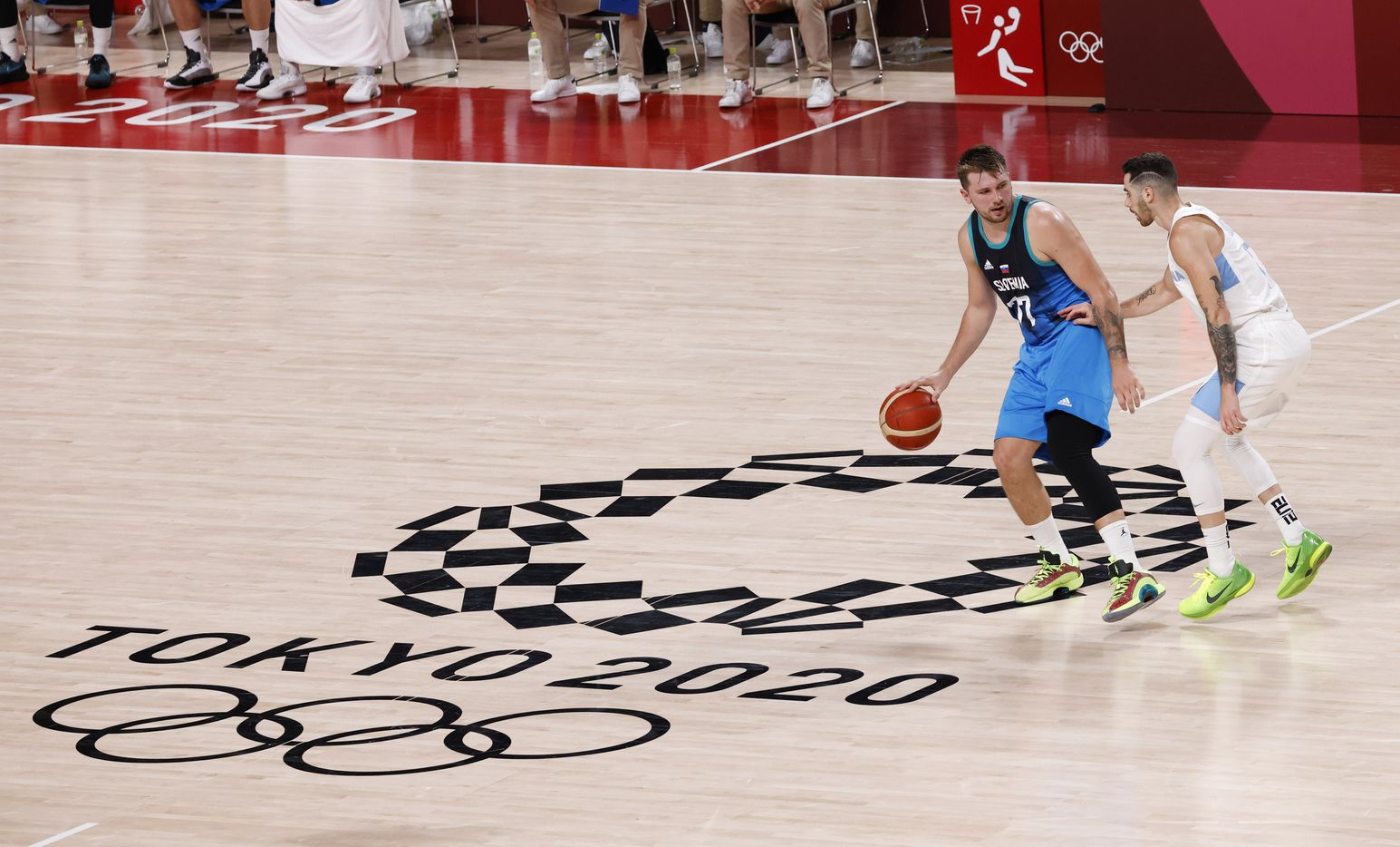 Slovenia's Luka Doncic (77) brings the ball up the court as Argentina's Luca Vildoza (17) defends in the second half of play during the postponed 2020 Tokyo Olympics at Saitama Super Arena on Monday, July 26, 2021, in Saitama, Japan. Slovenia defeated Argentina 118-100. (Vernon Bryant/The Dallas Morning News)