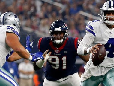 Dallas Cowboys quarterback Dak Prescott (4) scrambles out of the pocket under pressure from Houston Texans' Carlos Watkins (91) in the first half of a preseason NFL football game in Arlington, Texas, Saturday, Aug. 24, 2019.